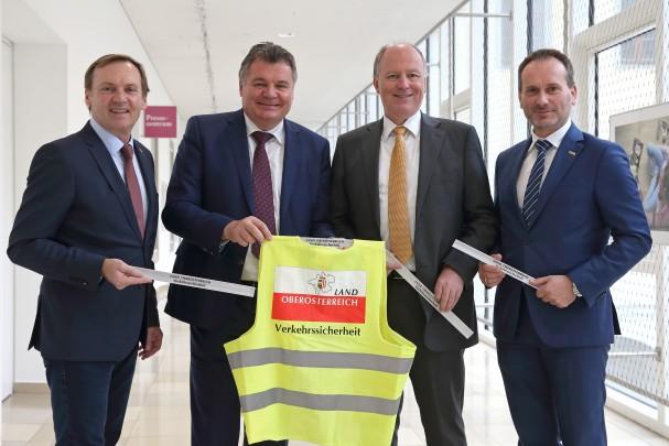 Politiker mit Warnwesten fordern Radfahrende auf sich sichtbar zu machen